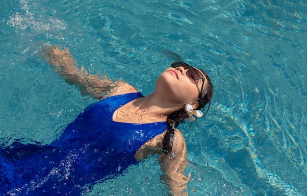 Menina asiática com piscina e óculos de sol na piscina