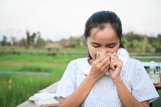 Menina asiática com sensação de febre fria da doença para o conceito de vírus corona