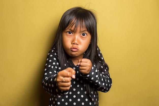 Menina asiática com soco no punho para lutar contra um ataque agressivo e raivoso