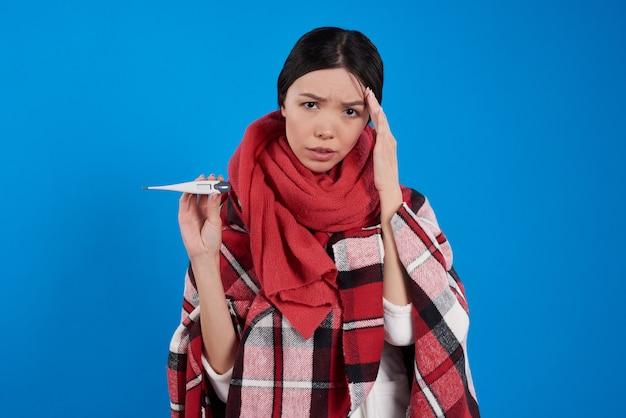 Menina asiática com temperatura de tomada fria isolada.