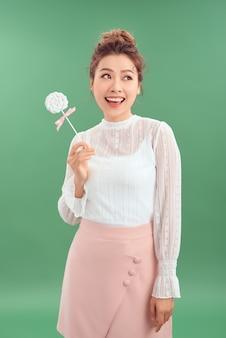 Menina asiática com um grande doce no palito, com um pirulito na mão