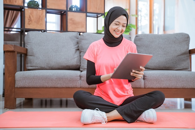 Menina asiática com uma roupa de ginástica com véu e um sorriso olhando para um tablet antes de fazer exercícios em casa