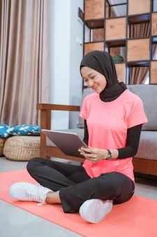 Menina asiática com uma roupa de ginástica de véu com um sorriso olhando para um tablet sentada no chão com um tapete antes dos exercícios internos em casa