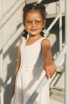 Menina asiática com vestido branco e óculos escuros na escada branca