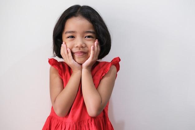 Menina asiática com vestido vermelho, mostrando um gesto fofo