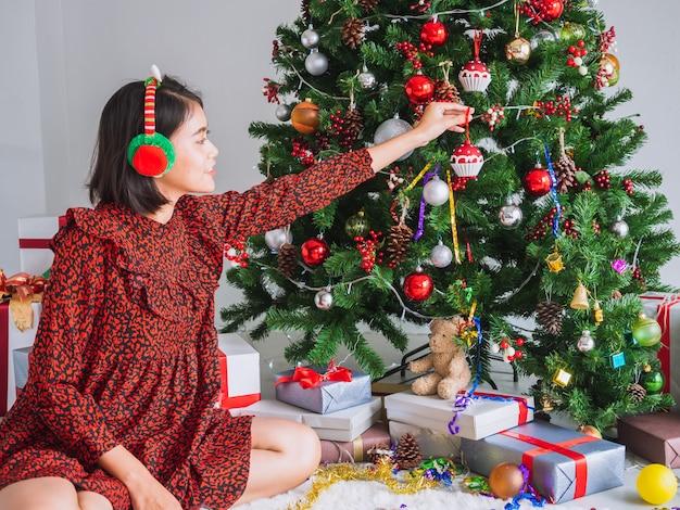 Menina asiática comemorando o natal em casa, mulher decorar a árvore de natal