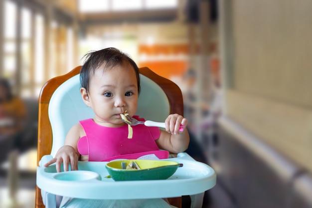 Menina asiática comendo comida na mesa do bebê.