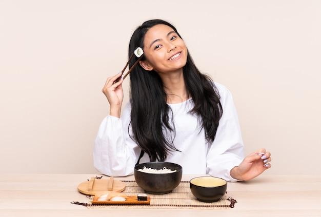 Menina asiática comendo macarrão e sushi