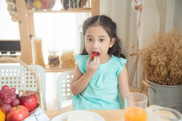 Menina asiática comendo morango na mesa de café da manhã