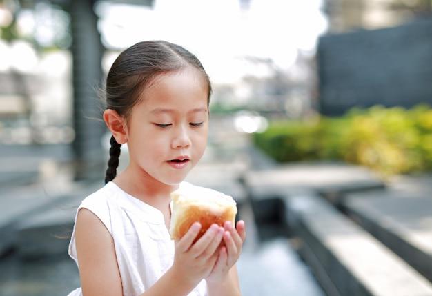 Menina asiática comendo pão com morango recheado