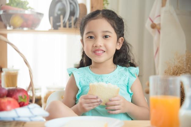 Menina asiática comendo pão na mesa de café da manhã