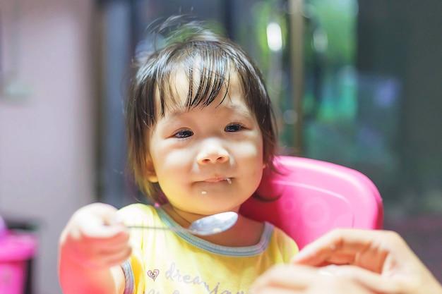 Menina asiática comendo salsichas fritas na tigela de alumínio perto da janela em casa