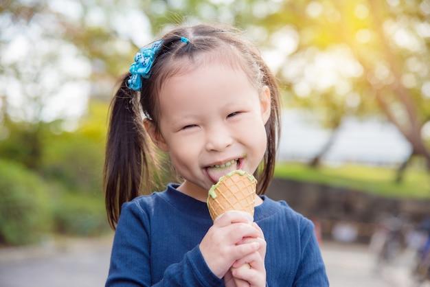 Menina asiática comendo sorvete de chá verde e sorrisos no parque
