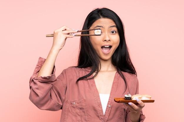 Menina asiática comendo sushi com pauzinhos