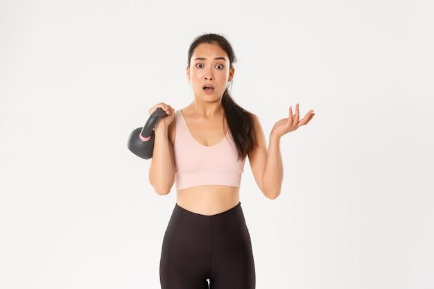 Menina asiática confusa da aptidão, atleta levantando o kettlebell e parece intrigada, consultando o treinador durante a sessão de treinamento, fundo branco de pé.