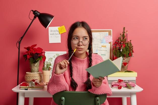 Menina asiática contemplativa séria com tranças penteadas, segura caderno e lápis, escreve planos futuros e metas para o natal