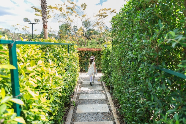 Menina asiática correndo no jardim