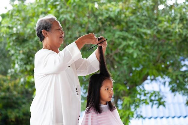 Menina asiática cortando o cabelo