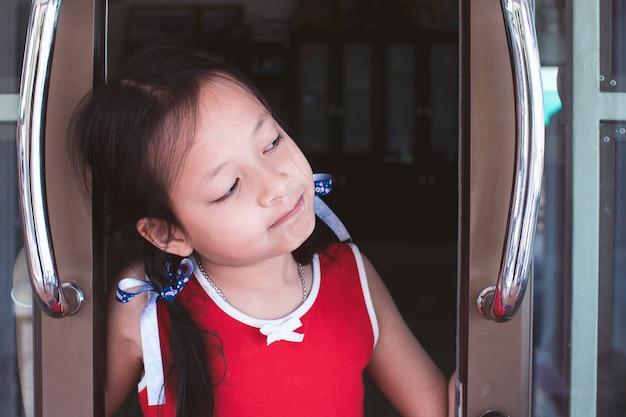 Menina asiática criança abrir a porta com olhando e esperando por alguém