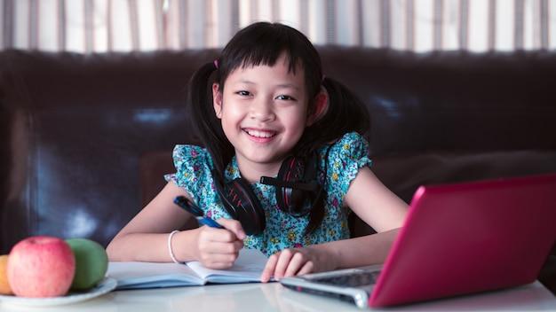Menina asiática criança cute estudando lição on-line em casa, distância social durante a quarentena, conceito de educação on-line. estilo 16: 9