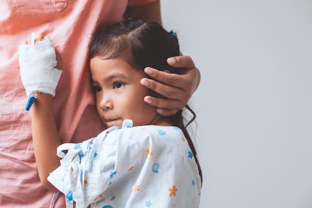Menina asiática criança doente que tem solução iv bandaged abraçando sua mãe