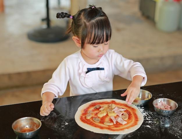 Menina asiática criança fazendo pizza