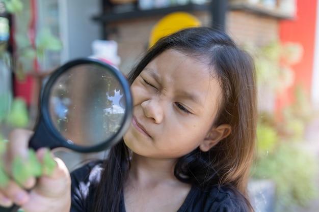Menina asiática criança olhando através de uma lupa
