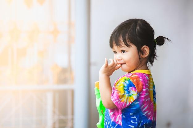Menina asiática criança se divertindo para jogar água com pistola de água no festival de songkran tailândia