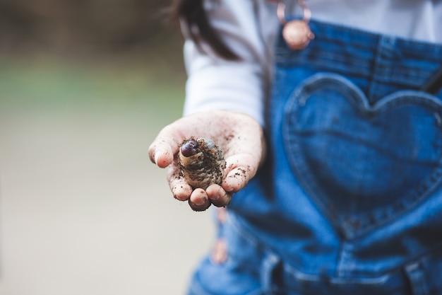 Menina asiática criança segurando larvas de besouro rinoceronte por lado com curioso e divertido