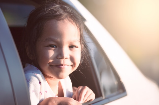 Menina asiática criança sorrindo e se divertindo para viajar de carro e olhando para fora da janela do carro