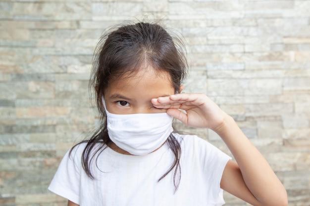 Menina asiática criança usando máscara de proteção e esfregando os olhos. ela fica em quarentena em casa contra o coronavírus covid-19 e a poluição do ar pm2.5. poluição do ar e conceito médico.