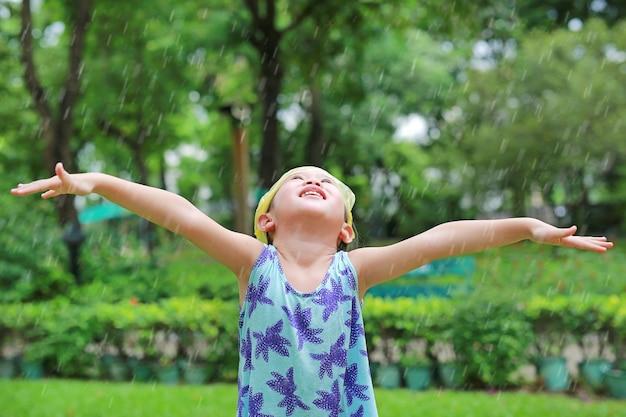 Menina asiática criança usar saco plástico na cabeça se divertindo para jogar com chuva no jardim