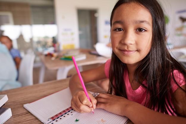 Menina asiática criando em seu caderno