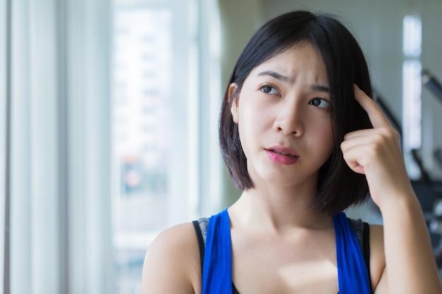 Menina asiática curiosa em uniforme de esporte pensando