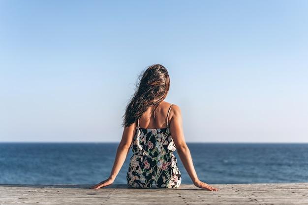 Menina asiática da bandeja bonita no vestido que senta-se no cais perto do mar.