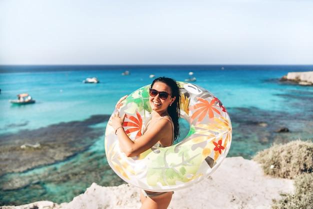 Menina asiática da bandeja consideravelmente feliz com flutuador grande e mar azul atrás no fundo.