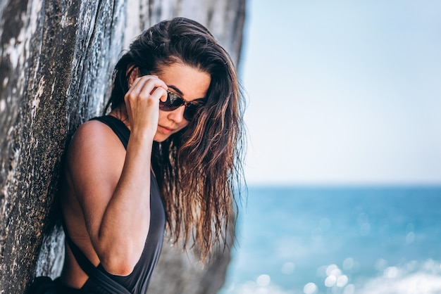 Menina asiática da bandeja moreno bonita no roupa de banho preto que relaxa sob a rocha na praia.