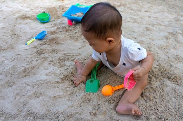 Menina asiática da criança bebê tailandês brincando com areia