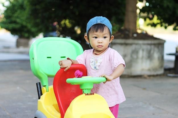 Menina asiática da criança do bebê que joga um brinquedo do carro no campo de jogos.
