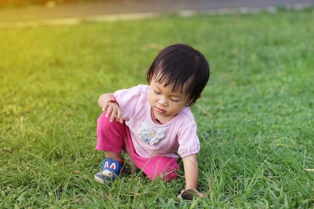 Menina asiática da criança do bebê que senta-se na terra.