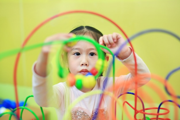 Menina asiática da criança do close-up que joga o brinquedo educacional para o desenvolvimento do cérebro na sala das crianças.