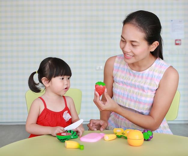 Menina asiática da criança e mãe jogando frutas de plástico no quarto do garoto