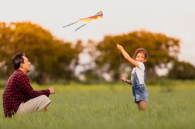 Menina asiática da criança e pai com um papagaio correndo e feliz no prado
