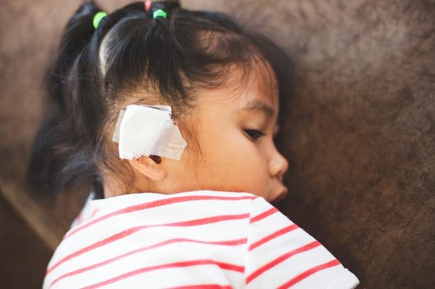 Menina asiática da criança ferida na orelha. ouvido da criança com bandagem após ter sido um acidente.