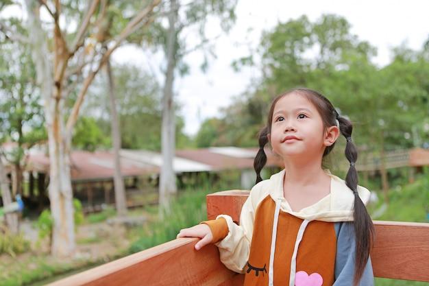 Menina asiática da criança na roupa morna no balcão.