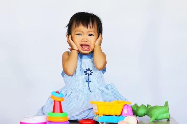 Menina asiática da criança que grita e que joga com muitos brinquedos.