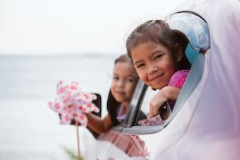 Menina asiática da criança que joga com a turbina de vento do brinquedo com sua irmã quando viajar de carro para a praia