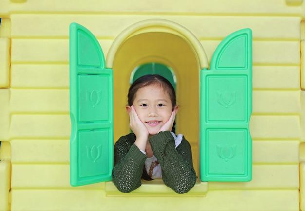 Menina asiática da criança que joga com o teatro do brinquedo da janela no campo de jogos.