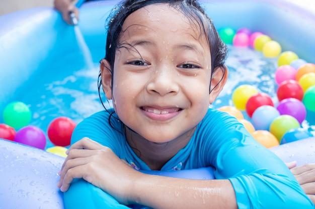Menina asiática da criança que tem o divertimento na associação de remo do jardim com wather da suficiência do pai no fundo.