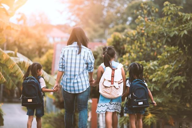 Menina asiática da mãe e da filha da pupila com a trouxa que guarda a mão e que vai à escola